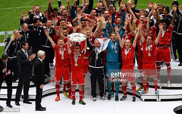 Philipp Lahm of Bayern Muenchen lifts the Bundesliga trophy with his teammates following their match against Augsburg at the Allianz Arena on May 11...