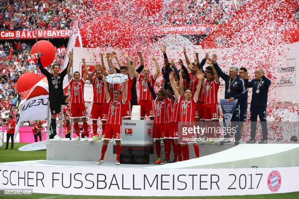 Philipp Lahm of Bayern Muenchen lifts the Championship trophy in celebration of the 67th German Championship title following the Bundesliga match...