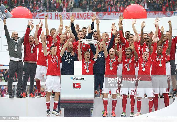 Philipp Lahm of Bayern Muenchen lifts the trophy as he celebrates victory with team mates after the Bundesliga match between FC Bayern Muenchen and...