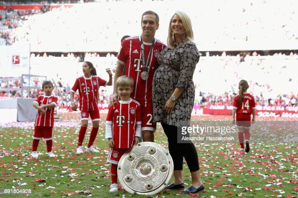 Philipp Lahm of Bayern Muenchen poses with his wife Claudia and son Julian with the Championship trophy in celebration of the 67th German...