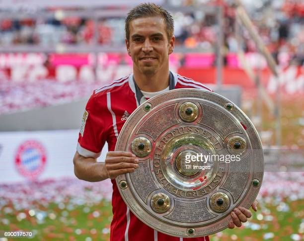 Philipp Lahm of Bayern Muenchen poses with the Championship trophy in celebration of the 67th German Championship title following the Bundesliga...