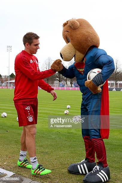 Philipp Lahm of Bayern Muenchen reacts with mascot Bernie dressed as Superman prior to a training session at Bayern Muenchen's training ground...