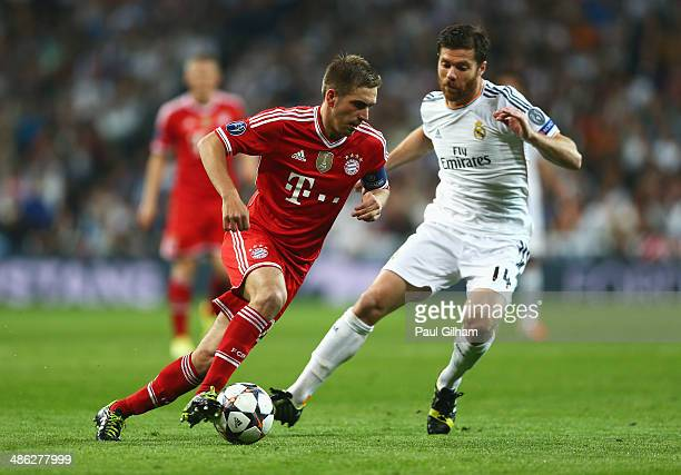 Philipp Lahm of Bayern Muenchen takes on Xabi Alonso of Real Madrid during the UEFA Champions League semifinal first leg match between Real Madrid...