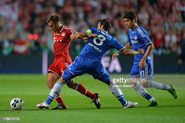 Philipp Lahm of Bayern Munich is marshalled by Frank Lampard and Oscar of Chelsea during the UEFA Super Cup between Bayern Muenchen and Chelsea at...