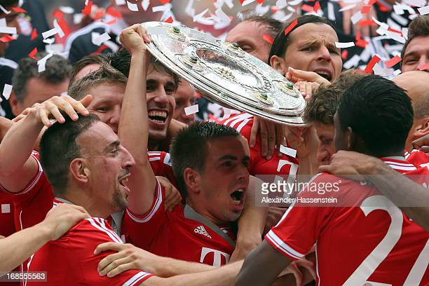 Philipp Lahm of FC Bayern Muenchen lifts the Bundesliga trophy following his team's match against Augsburg at the Allianz Arena on May 11 2013 in...