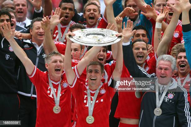 Philipp Lahm of FC Bayern Muenchen lifts the Bundesliga trophy with his team mates Bastian Schweinsteiger and head coach Jupp Heynckes following his...