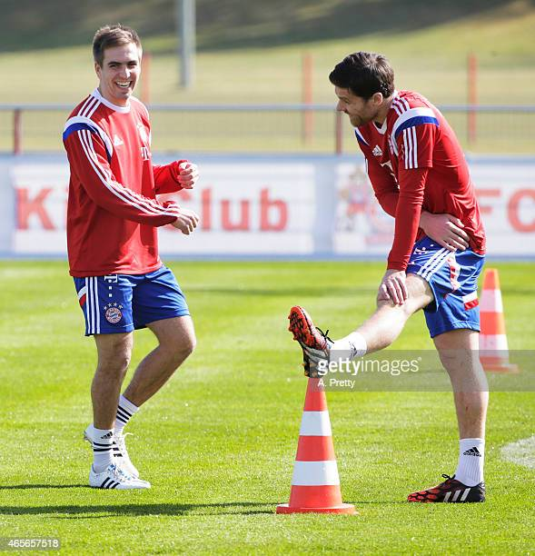 Philipp Lahm of FC Bayern Muenchen shares a laugh with Xabi Alonso during training on March 9 2015 in Munich Germany