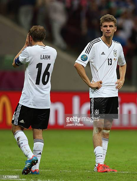 Philipp Lahm of Germany and Thomas Muller of Germany show their dejection after the UEFA EURO 2012 semi final match between Germany and Italy at the...
