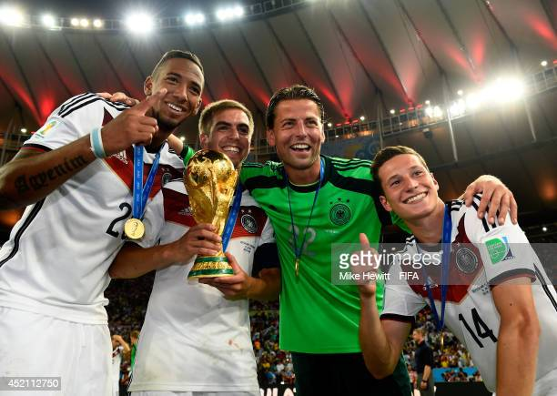 Philipp Lahm of Germany holds the World Cup to celebrate with his teammates Jerome Boateng Roman Weidenfeller and Julian Draxler after the 2014 FIFA...