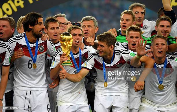 Philipp Lahm of Germany holds the World Cup trophy while posing for photographs with his teammates after the 2014 FIFA World Cup Brazil Final match...
