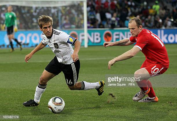 Philipp Lahm of Germany is chased by Wayne Rooney of England during the 2010 FIFA World Cup South Africa Round of Sixteen match between Germany and...