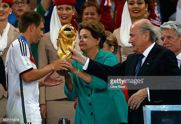 Philipp Lahm of Germany is presented with the World Cup trophy by Brazilian President Dilma Rousseff and FIFA President Joseph S Blatter after...
