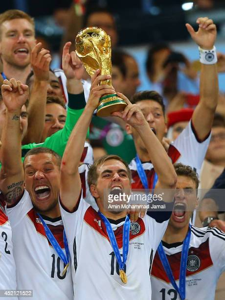 Philipp Lahm of Germany lifts the World Cup trophy and celebrates with teammates after defeating Argentina 10 in extra time during the 2014 FIFA...