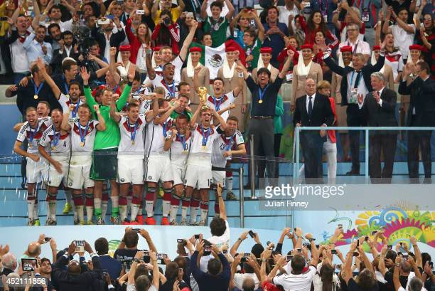 Philipp Lahm of Germany lifts the World Cup trophy with teammates after defeating Argentina 10 in extra time as FIFA President Joseph S Blatter and...
