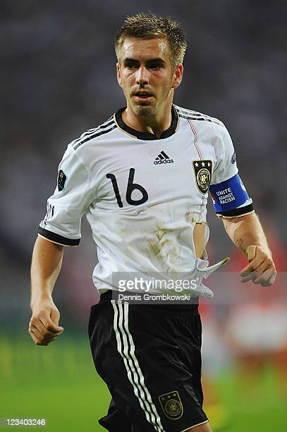 Philipp Lahm of Germany plays with a damaged shirt during the UEFA EURO 2012 qualifying match between Germany and Austria at VeltinsArena on...