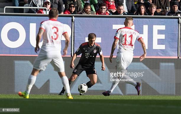 Philipp Lahm of Muenchen is challenged by Jonathan Schmid of Augsburg during the Bundesliga match between FC Augsburg and Bayern Muenchen at WWK...