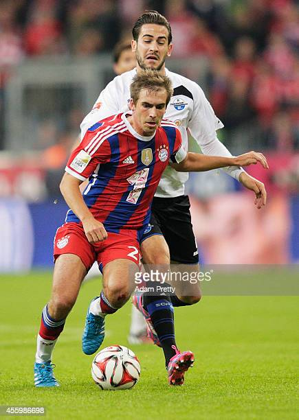 Philipp Lahm of Muenchen is challenged by Mario Vrancic of Paderborn during the Bundesliga match between FC Bayern Muenchen and SC Paderborn 07 at...