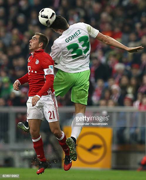 Philipp Lahm of Muenchen jumps for a header with Mario Gomez of Wolfsburg during the Bundesliga match between Bayern Muenchen and VfL Wolfsburg at...
