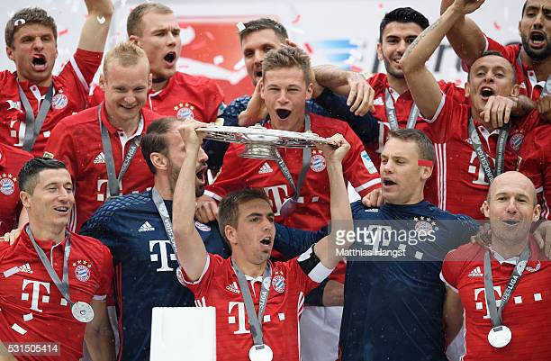 Philipp Lahm of Muenchen lifts the Meisterschale as players and staffs celebrate the Bundesliga championship after the Bundesliga match between FC...