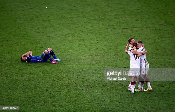 Philipp Lahm Thomas Mueller and Bastian Schweinsteiger of Germany celebrate as a dejected Sergio Aguero of Argentina lies on the pitch after...