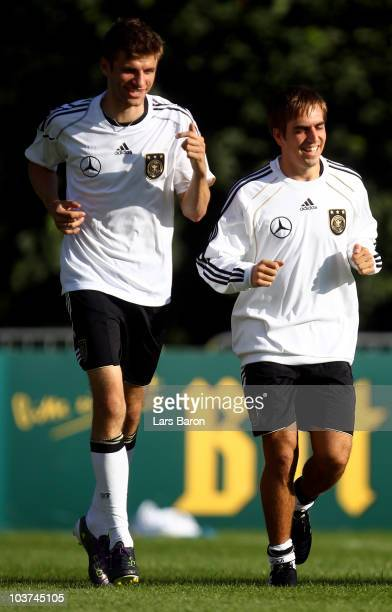 Philipp Lahm warms up with Thomas Mueller during the Germany training session at Commerzbank Arena on August 31 2010 in Frankfurt am Main Germany