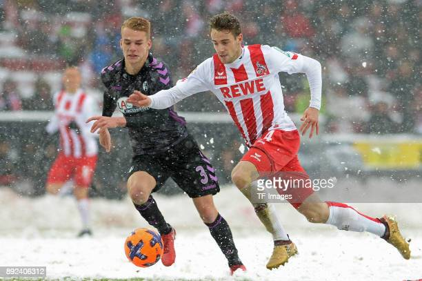 Philipp Lienhart of Freiburg and Lukas Kluenter of Koeln battle for the ball during the Bundesliga match between 1 FC Koeln and SportClub Freiburg at...