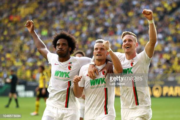 Philipp Max of Augsburg celebrates with teammates after scoring his team's second goal during the Bundesliga match between Borussia Dortmund and FC...