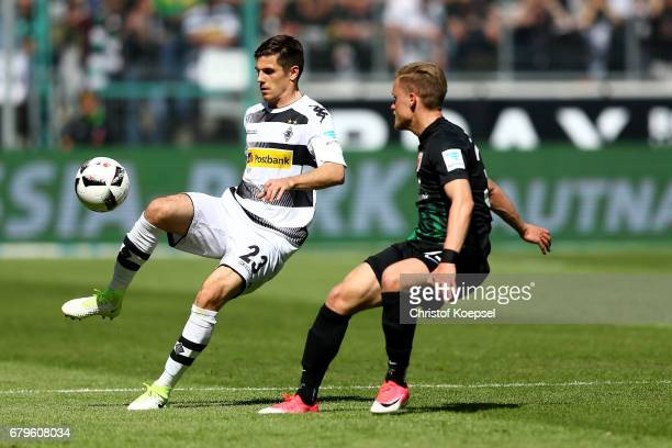 Philipp Max of Augsburg challenges Jonas Hofmann of Moenchengladbach during the Bundesliga match between Borussia Moenchengladbach and FC Augsburg at...
