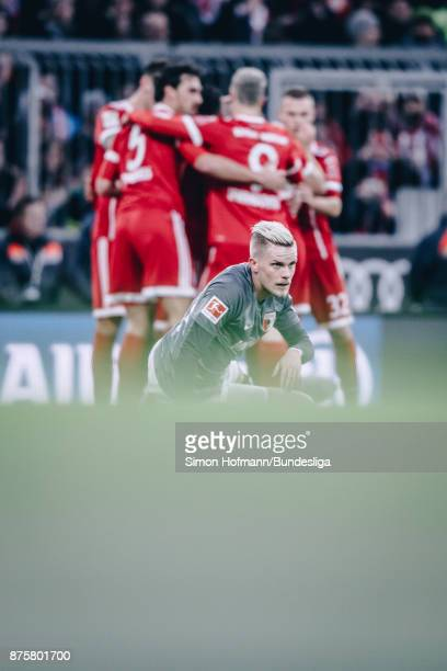 Philipp Max of Augsburg is disappointed as team mates of Muenchen celebrate their first goal during the Bundesliga match between FC Bayern Muenchen...