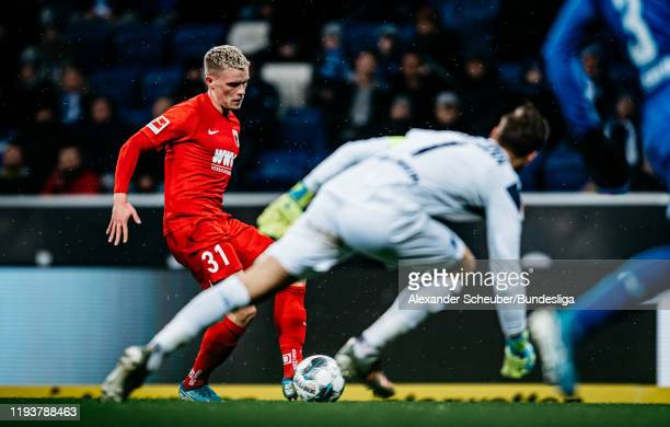 Philipp Max of Augsburg scores the first goal for his team against Oliver Baumann of Hoffenheim during the Bundesliga match between TSG 1899...