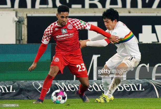 Philipp Mwene of Mainz is challenged by Wataru Endo of Stuttgart during the Bundesliga match between VfB Stuttgart and 1. FSV Mainz 05 at...