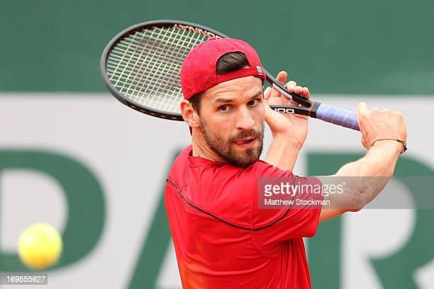 Philipp Petzschner of Germany plays a backhand during his Men's Singles match against Marin Cilic of Croatia during day two of the French Open at...