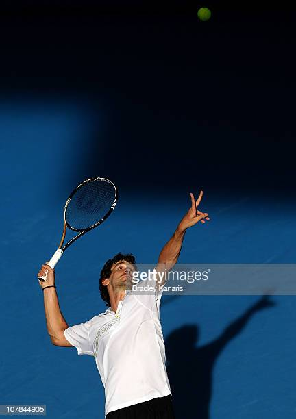 Philipp Petzschner of Germany serves during his first round match against Feliciano Lopez of Spain during day one of the Brisbane International at...