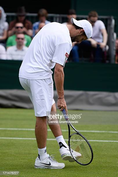 Philipp Petzschner of Germany taps his foot with his racquet during his Gentlemen's Singles first round match against Michal Przysiezny of Poland on...