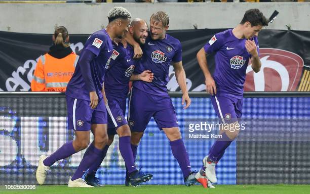 Philipp Riese of Aue celebrates with teammates after scoring his team's first goal during the Second Bundesliga match between SG Dynamo Dresden and...