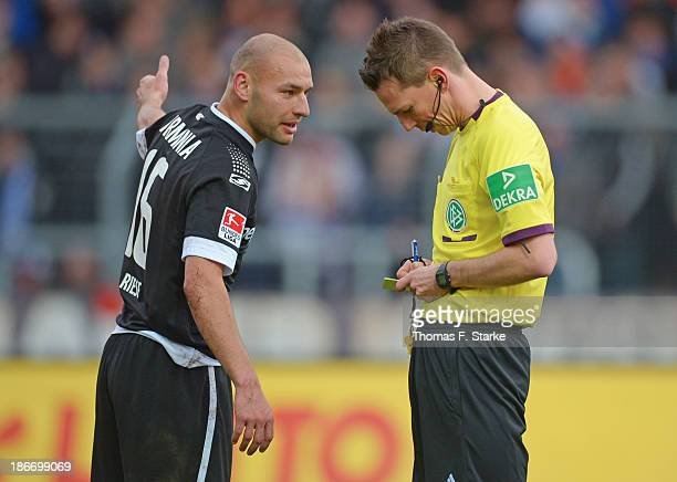 Philipp Riese of Bielefeld argues with referee Christian Bandurski during the Second Bundesliga match between Karslruher SC and Arminia Bielefeld at...