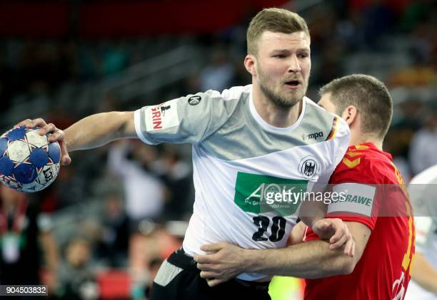 Philipp Weber of Germany vies for the ball with Igor Radojevic of Montenegro during the preliminary round group C match of the Men's 2018 EHF...
