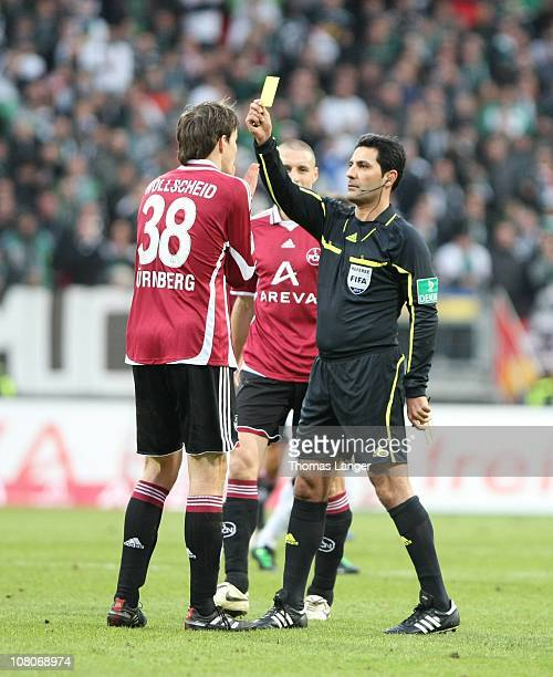 Philipp Wollscheid of Nuremberg is fined with the yellow card by referee Babak Rafati during the Bundesliga match between 1 FC Nuernberg and Borussia...