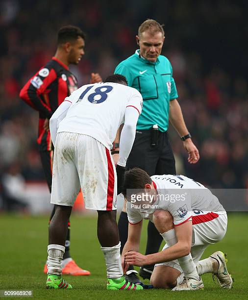 Philipp Wollscheid of Stoke City does up the shoelaces for Mame Biram Diouf during the Barclays Premier League match between AFC Bournemouth and...