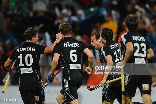 Philipp Zeller of Germany celebrates with team mates after scoring his team's opening goal during the Men's Eurohockey 2011 semi final match between...