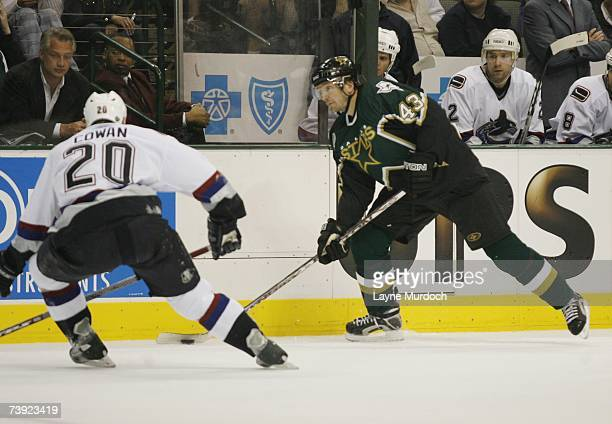 Philippe Bouher of the Dallas Stars plays the puck as Jeff Cowan of the Vancouver Canucks defends during game three of the 2007 NHL Western...