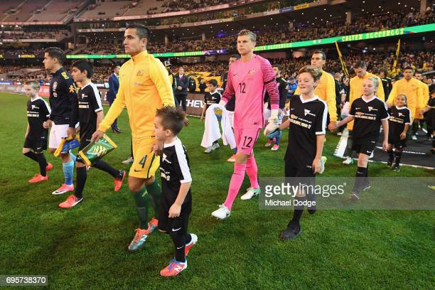 Philippe Correia of Brazil and Tim Cahill of the Socceroos lead the teams out during the Brasil Global Tour match between Australian Socceroos and...