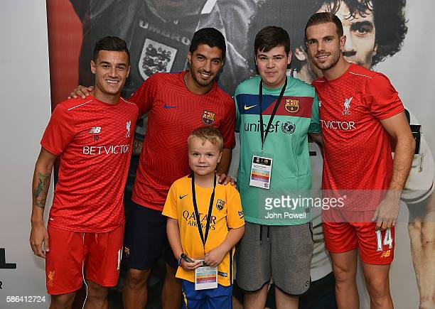 Philippe Coutinho and Jordan Henderson of Liverpool with Luis Suarez of Barcelona and Mark Waghorn and Leon Childs from the Make a Wish Foundation...
