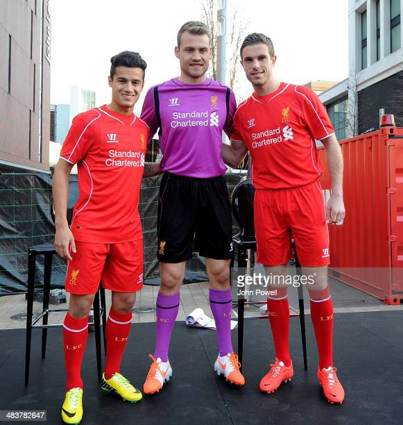 Philippe Coutinho Jordan Henderson and Simon Mignolet of Liverpool present the new home kit for next season at Liverpool One on April 10 2014 in...