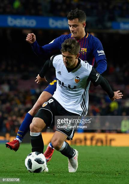 Philippe Coutinho of Barcelona competes for the ball with Luciano Vietto of Valencia during the Copa del Rey semifinal first leg match between FC...