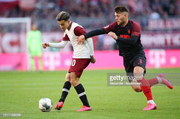 Philippe Coutinho of Bayern Munich battles for possession with Eduard Lowen of Augsburg during the Bundesliga match between FC Bayern Muenchen and FC...