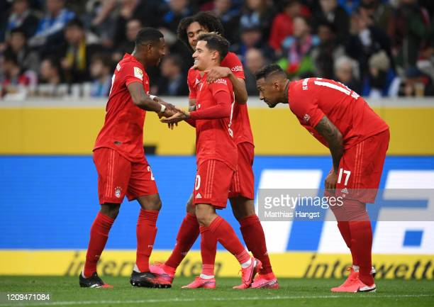 Philippe Coutinho of Bayern Munich celebrates with teammates Joshua Zirkzee and David Alaba during the Bundesliga match between TSG 1899 Hoffenheim...