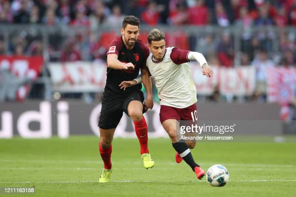 Philippe Coutinho of Bayern Munich runs with the ball past Rani Khedira of Augsburg during the Bundesliga match between FC Bayern Muenchen and FC...