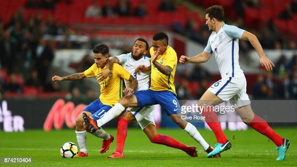 Philippe Coutinho of Brazil and Gabriel Jesus of Brazil battle for possession with Ryan Bertrand of England during the international friendly match...