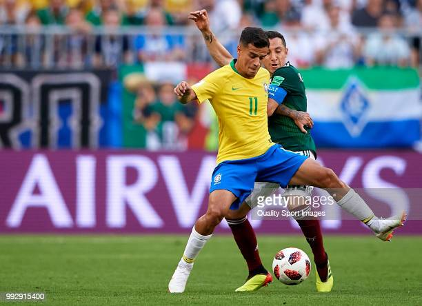 Philippe Coutinho of Brazil competes for the ball with Andres Guardado of Mexico during the 2018 FIFA World Cup Russia Round of 16 match between...